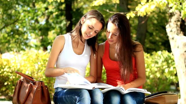 vídeos y material grabado en eventos de stock de dos chica adolescente aprendiendo juntos al aire libre - only teenage girls