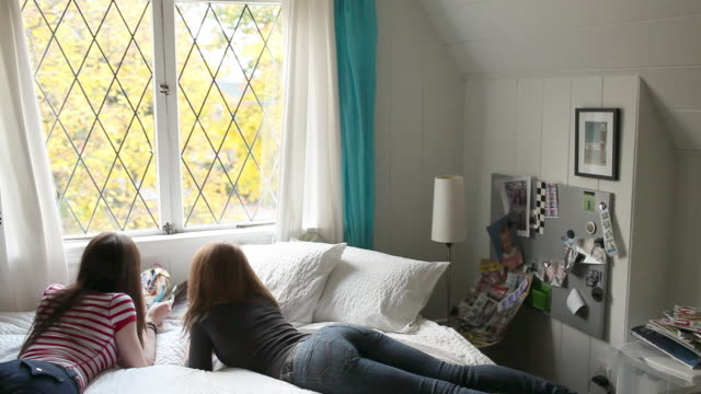 Two teenage girls lying on bed reading magazines
