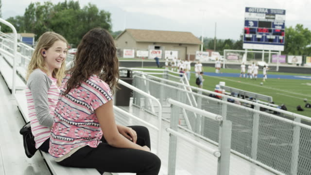 Two teenage girls on the bleacher's talking and laughing.