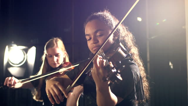 Two teenage girls playing violin in concert