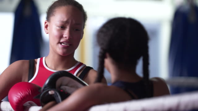 two teenage girls relaxing in boxing ring, chatting after exercising - 女子ボクシング点の映像素材/bロール