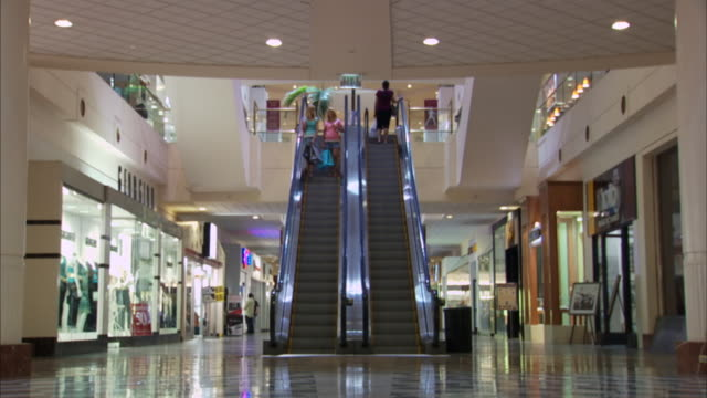 LA WS Two teenage girls riding down escalator and then walking in shopping mall / Los Angeles, CA, USA
