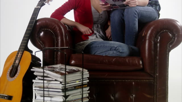 two teenage girls spending time in an armchair. - sideways glance stock videos and b-roll footage