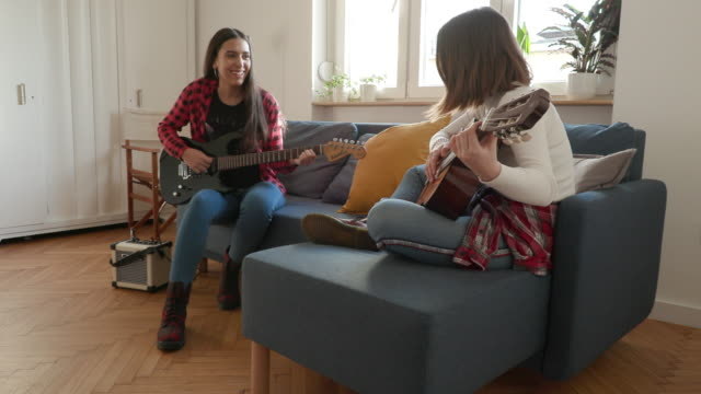 two teenage girls trying to learn guitar chords at home - amateur stock videos & royalty-free footage