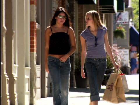 vídeos de stock, filmes e b-roll de two teenage girls walking on the road - gastando dinheiro