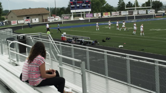 vídeos de stock e filmes b-roll de two teenage girls watching girls' soccer practice from the bleachers. - banco assento