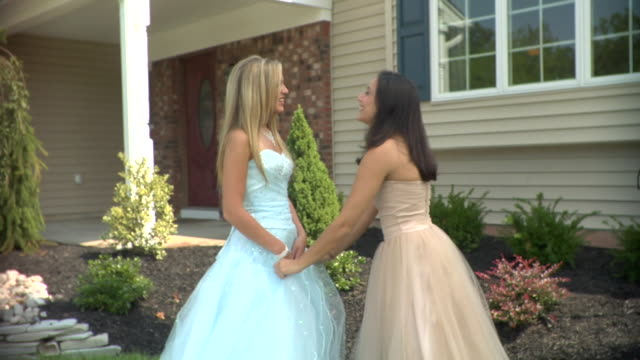 ms, two teenage girls (16-17) wearing prom dresses in front of house, edison, new jersey, usa - 2000s style点の映像素材/bロール
