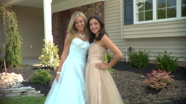ms, two teenage girls (16-17) wearing prom dresses posing in front of house, portrait, edison, new jersey, usa - high school prom stock videos and b-roll footage