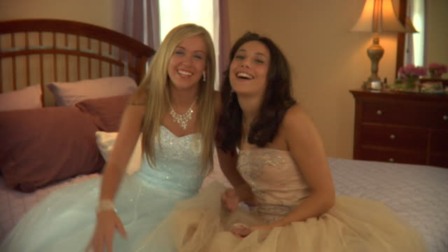 MS, Two teenage girls (16-17) wearing prom dresses sitting on bed, portrait, Edison, New Jersey, USA