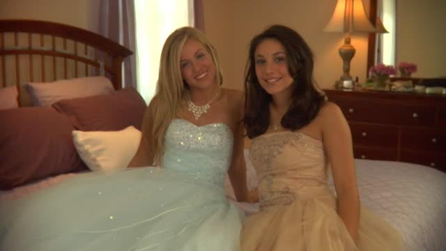 ms, two teenage girls (16-17) wearing prom dresses sitting on bed, portrait, edison, new jersey, usa - 少於10秒 個影片檔及 b 捲影像