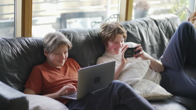 two teenager boys together on the sofa working on their school work - variation stock videos & royalty-free footage