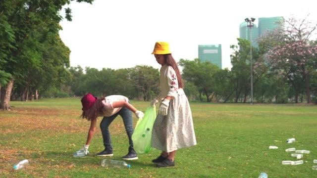 2人のティーンエイジャーの女の子は、公園でボトルなどのリサイクル廃棄物をリサイクルリサイクルリサイクルを選ぶのに役立ちます - ゴミ袋点の映像素材/bロール