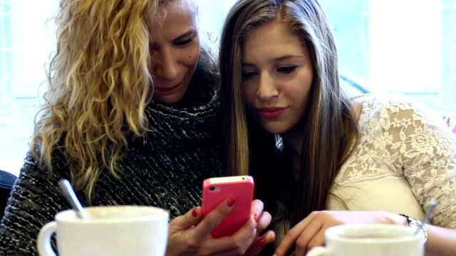 two teenager girls looking pictures on a cell phone - white shirt stock videos & royalty-free footage