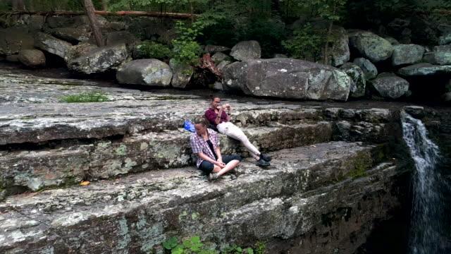 två tonåring flickor vilar på toppen av berget nära av vattenfall. drone video med orbit kamerarörelserna - poconobergen bildbanksvideor och videomaterial från bakom kulisserna