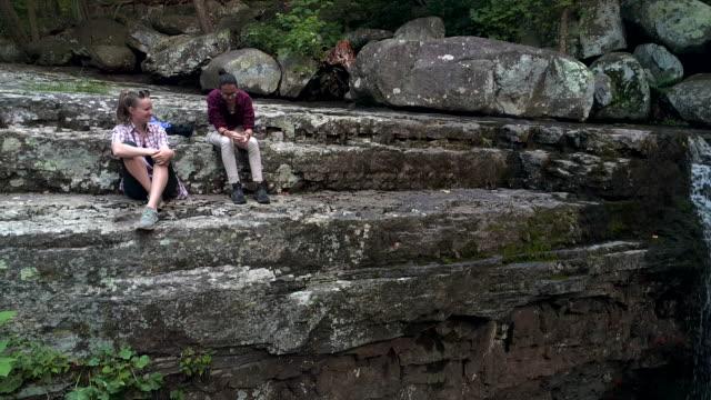 två tonåring flickor vilar på toppen av berget nära av vattenfall. drone video med fallande kamera - poconobergen bildbanksvideor och videomaterial från bakom kulisserna