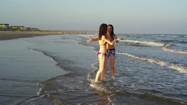Two teenager girls runs and plays in the water at the ocean beach