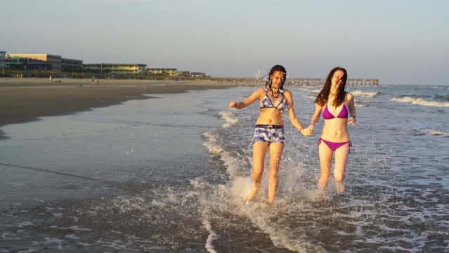 two teenager girls runs and plays in the water at the ocean beach - south carolina stock videos & royalty-free footage