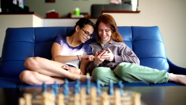 two teenager girls, sisters, browsing social media together - child sitting cross legged stock videos & royalty-free footage