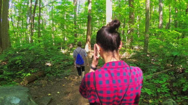 two teenager girls walking through the forest - amicizia tra donne video stock e b–roll