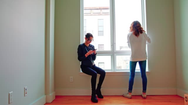 two teenager sisters exploring the new apartment. looking on the window in the empty room. - 18 19 years stock videos and b-roll footage