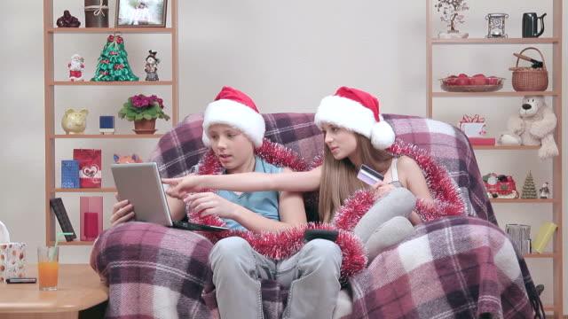 Two teenager wearing Santa Claus hats, buying something in internet.