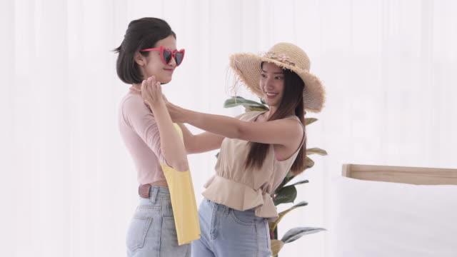 stockvideo's en b-roll-footage met twee tieners kiezen voor de outfits die op vakantie gedragen zullen worden. - dragen