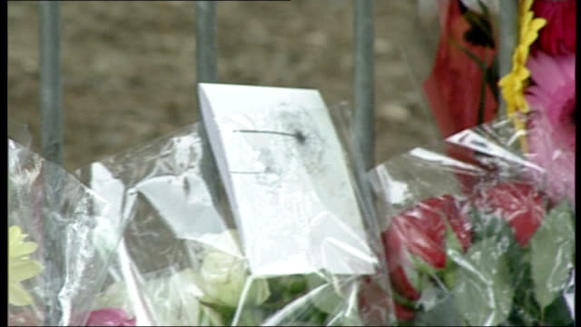 two teenagers die after being struck by a train in hertfordshire; hertfordshire: borehamwood: ext entrance to hertswood academy floral tributes... - ボーハムウッド点の映像素材/bロール