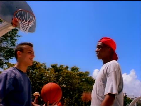 vídeos de stock, filmes e b-roll de two teenagers high-five each other on an outdoor basketball court. - 1990