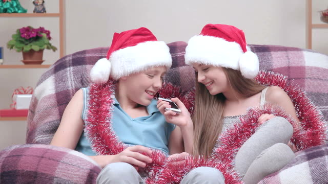 Two teenagers in Santa Claus hats and glistening talking speakerphone