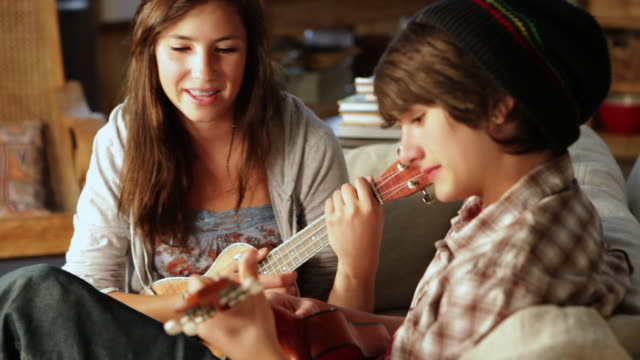 ms two teenagers learning to play ukulele together / lamy, new mexico, united states - gitarre stock-videos und b-roll-filmmaterial