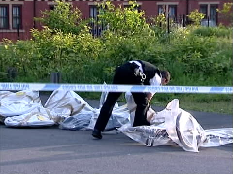 vidéos et rushes de investigation continues england manchester arwick ext bicycles lying on footpath pan to police forensic officer in white overalls taking evidence... - salopette