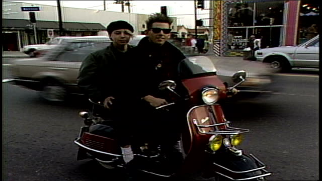 Two Teens on a Vespa Scooter then Drive off Down Street in Los Angeles California