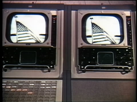 1962 two television monitors showing American flag / broadcast from first communications satellite