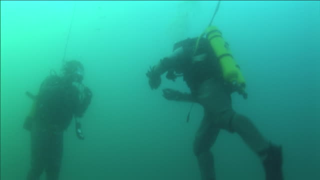 two tethered scuba divers carry on a conversation underwater. - aqualung diving equipment stock videos & royalty-free footage