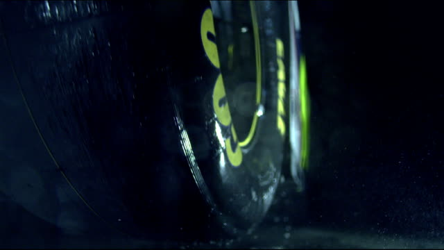 vídeos de stock, filmes e b-roll de two tires w/ yellow goodyear logo on suspended race car one large wet tire in focus spinning in fg w/ water droplets flying off one soft tire in bg... - soft focus