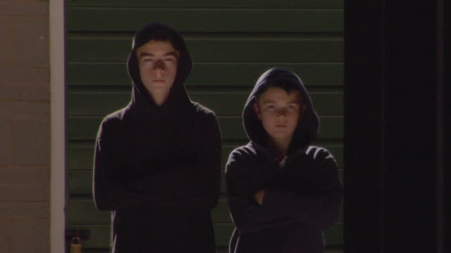 ms two tough-looking boys wearing hoodies, then older one leaves / london, england - mischief stock videos & royalty-free footage