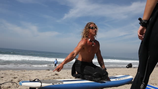 Two tourists from Germany get their first surf lessons on the beach of Venice Beach in Los Angeles California USA