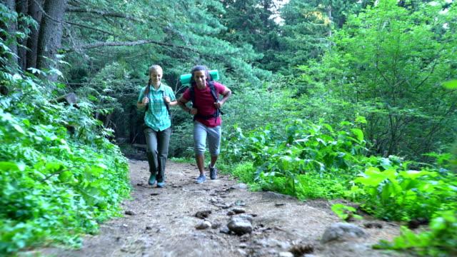 モミの木の森を歩いてバックパックと 2 つの観光客