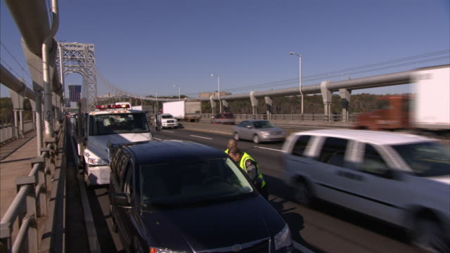 two tow-truck drivers stand by a parked car on the side of a busy freeway. - tow truck stock videos and b-roll footage