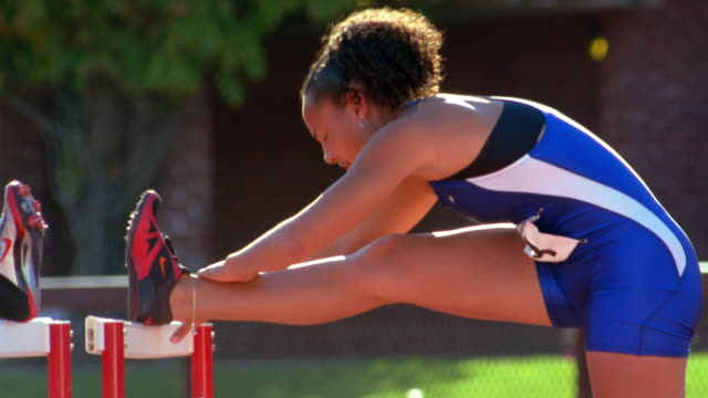 two track and field athletes use the hurdles to stretch their legs. - warming up stock videos and b-roll footage