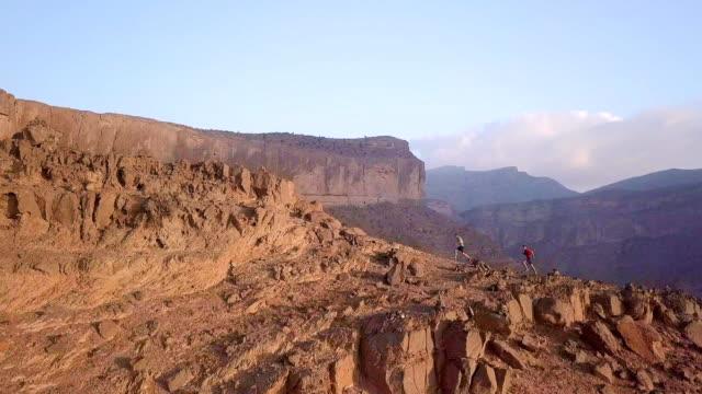 vídeos y material grabado en eventos de stock de dos trail runner ascendiendo la cordillera sobre el cañón - omán