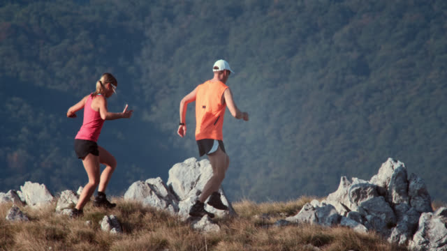Two trail runners going down the grassy plateau