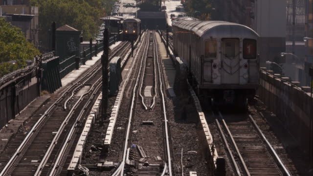 Two trains in Harlem, New York City move past on the above ground tracks