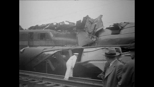 vídeos y material grabado en eventos de stock de / two trains in head on collision sit on the tracks / crowd surround the trains / victims removed on stretchers / cu twisted metal of the train /... - 1951