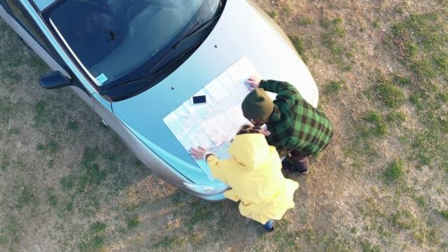 vidéos et rushes de deux voyageurs examinant la carte - capot de voiture