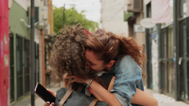 two traveling friends meeting up and hugging each other in the city - bright colour stock videos & royalty-free footage