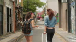 Two traveling friends walking down a city street together