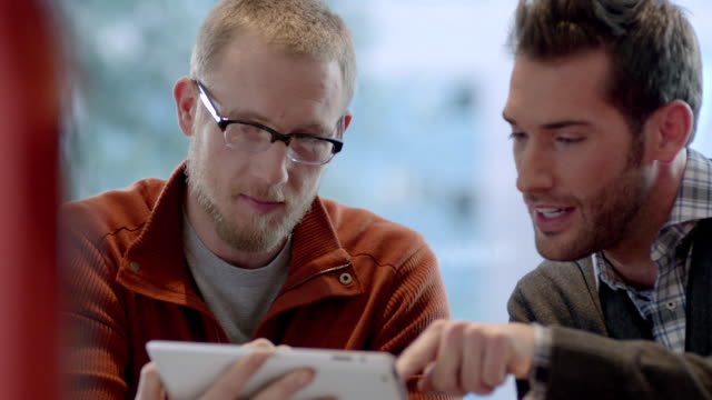 two trendy young businessmen strategize with tablet in large corporate office common area (close-up, dolly shot) - stoppelbart stock-videos und b-roll-filmmaterial