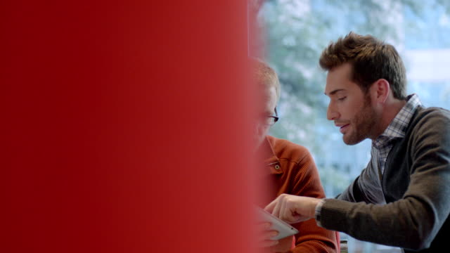 Two trendy young businessmen strategize with tablet in large corporate office common area (dolly shot)