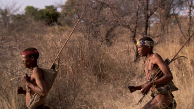 two tribesmen run through the bush. available in hd - hunter stock videos & royalty-free footage